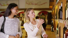4K cheerful women looking at bottles of wine on shelves in specialist wine store - stock footage