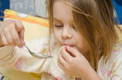 Stock Photo of Funny five year old girl eating spaghetti sitting in the crib