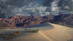 Death Valley Sand Dunes with Mountain Range and Background Clouds in Time Lapse Stock Footage
