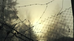 Wire netting surrounded by fog and sunrise Stock Footage