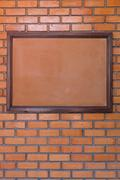 blank noticeboard message on brick wall background - stock photo