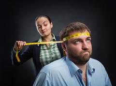 Businesswoman measuring man's head Stock Photos