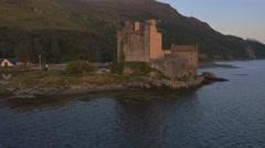 Aerial sunset view Eilean Donan castle Loch Duich Scotland Stock Footage