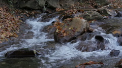 Mountain stream flowing and splashing big stones or rocks in water, slow motion. Stock Footage