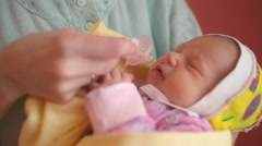 Mom gives the pacifier to a newborn baby - baby don't take the pacifier Stock Footage