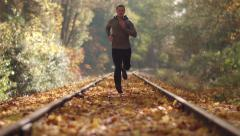 Man Jogging Up Train Tracks in Autumn Season with Leaves Falling - stock footage