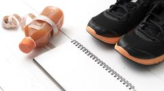 running shoes,orange juice,measuring tape and notepad - stock photo