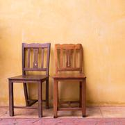 Stock Photo of wooden chair and cement mortar wall background