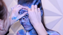 Removing mask from the face of body art model Stock Footage