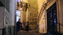 People walking by old street from Coimbra at night, Portugal slider Shot Stock Footage