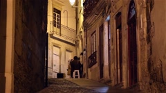 Street with people walking and sitting in a bar at night in Coimbra, Portugal Stock Footage