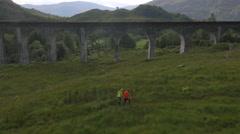 Aerial view of people by Glenfinnan railway Viaduct Scotland Stock Footage