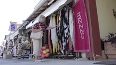Women looking to buy a scarf from a shop on the main street of the the touris Stock Footage