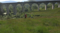 Aerial view of couple by Glenfinnan steam railway Viaduct Scotland Stock Footage