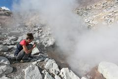 Girl photographing steaming fumarole on crater active volcano. Kamchatka, Russia Stock Photos