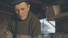 Old carpenter grandfather with old hands in the studio working on wood Stock Footage