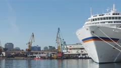 White cruise liner Europa docked in port with working port cranes on a backgroun Stock Footage