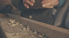 Senior craftsman working with planer on wooden pole in his workshop Stock Footage