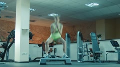 Athlete female doing squats and jumps on fitness step Stock Footage
