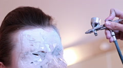 BodyArt Master makes mask on face model Stock Footage