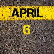 6 April calendar day over road marking yellow paint line - stock photo
