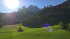 Aerial sun flare view St Johann church Rainui Dolomites Italy Stock Footage
