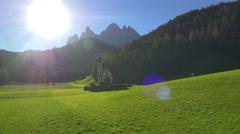 Aerial sun flare view St Johann chapel Alto Adige Dolomites Italy - stock footage