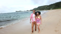 Loving young Caucasian couple holding hands walking together beach Oahu Hawai Stock Footage