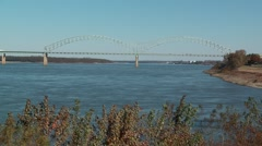 Trucks drive over a peaceful Mississippi River on the I40 Bridge Stock Footage
