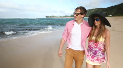 Loving young Caucasian couple holding hands walking together beach Oahu Hawaii - stock footage