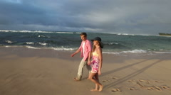 Loving young Caucasian couple holding hands walking together beach Oahu Hawaii Stock Footage
