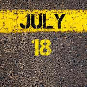 18 July calendar day over road marking yellow paint line - stock photo