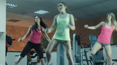 Aerobics class stepping together led by instructor at the gym Stock Footage