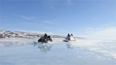 Snowmobiles towing qamutik traveling across sea ice at Admiralty Inlet. Stock Footage