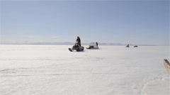 Snowmobiles pulling qamutiks across sea ice in the arctic. Stock Footage