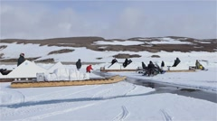An expedition team pulling qamutiks across leads with snowmobiles. - stock footage
