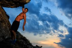 Free climber holding on the cliff Stock Photos