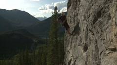 A rock climber scaling back down a mountain. Stock Footage