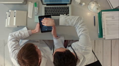 Top view of Doctors discussing images of x-ray scan on tablet - stock footage