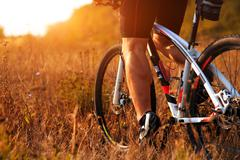 Cyclist man legs riding mountain bike on outdoor trail in autumn forest Stock Photos