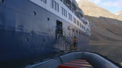 Zodiac boat slowly pulling up to an arctic cruise ship. Slow Motion Stock Footage