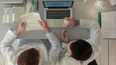 Stock Video Footage of Scientists looking attentively at pill in hospital. Top view
