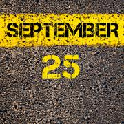 25 September calendar day over road marking yellow paint line - stock photo