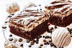 pieces of filled cake with chocolate icing - stock photo