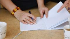 Female hand writes a pen in a notebook. Two girls - stock footage