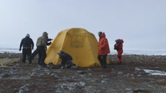 Expeditioner weighing down tent with rocks. Stock Footage