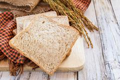 Spike and whole wheat bread on white wooden table - stock photo