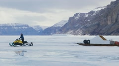Man on ski-doo tows expedition equipment across frozen sea. Pan Stock Footage