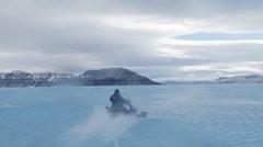 Arctic, Nunavut - Medium tracking shot of a man ski-dooing across water on se Stock Footage
