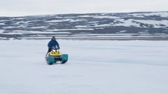 Man on ski-doo crossing frozen sea. Pan - stock footage